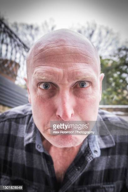 head shot of a bald man in his fifties pulling a face - ugly bald man stock pictures, royalty-free photos & images
