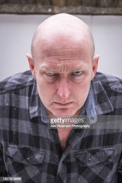 head shot of a bald man in his fifties pulling a moody face - ugly bald man stock pictures, royalty-free photos & images