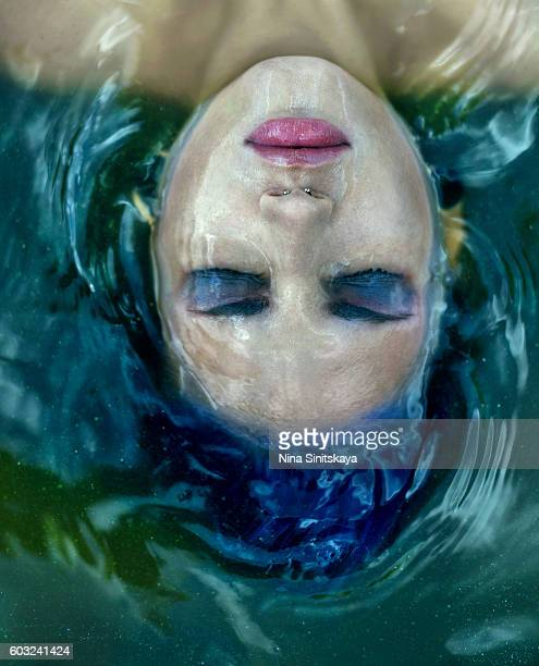Head shot of a woman with blue hair and make-up floating in water