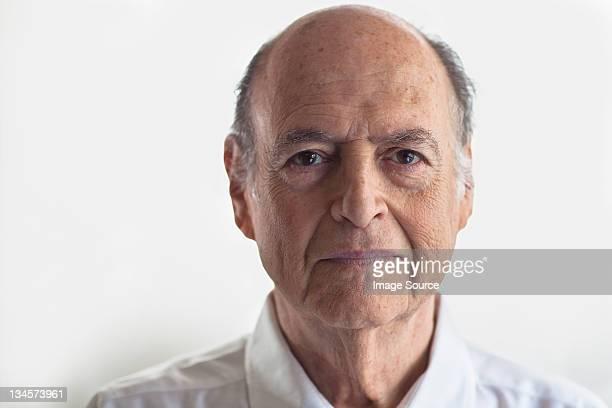 Head shot of senior man looking displeased