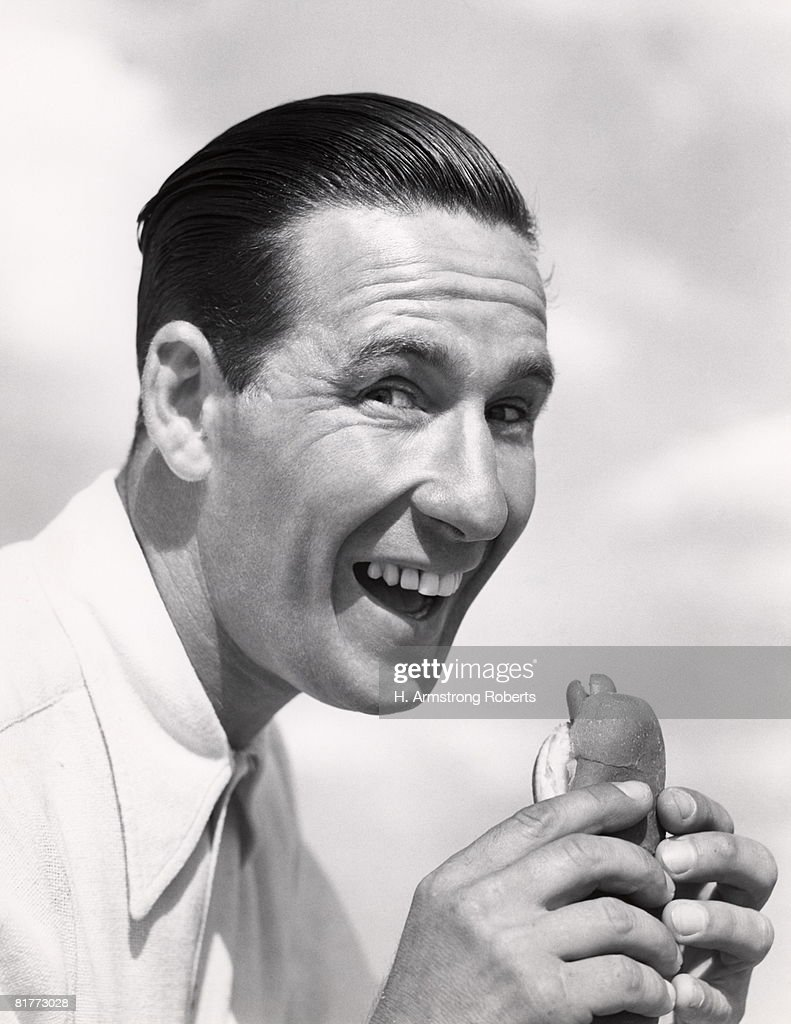 Head Shot Of Smiling Man With Wide Open Mouth And Head Pushed Forward About To Eat A Hotdog In A Frankfurter Roll Wearing A White Shirt Buck Teeth Hair. : Stock Photo
