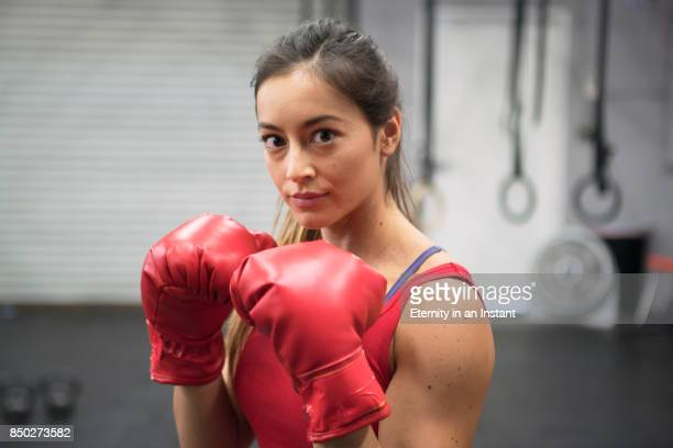 Head shot of young woman boxing in a gym