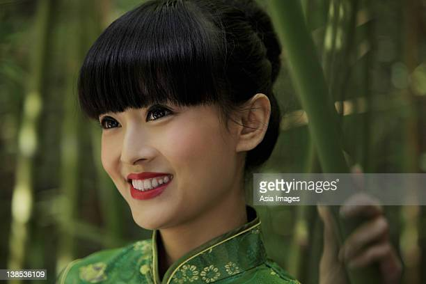 Head shot of young woman wearing a traditional Chinese dress and standing in front of bamboo trees.