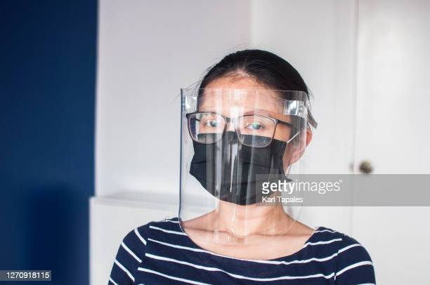 a head shot portrait of a young southeast asian woman employee in casual clothing, protective face mask and face shield in the office - filipino ethnicity and female not male fotografías e imágenes de stock