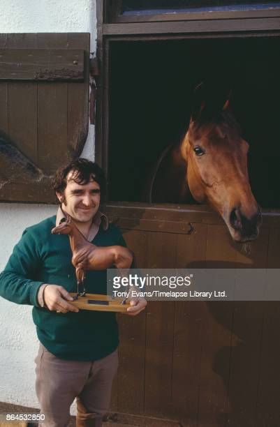 Head stable lad Barry Ellison holding a statuette and champion Thoroughbred steeplechaser racehorse 'Red Rum' 1975