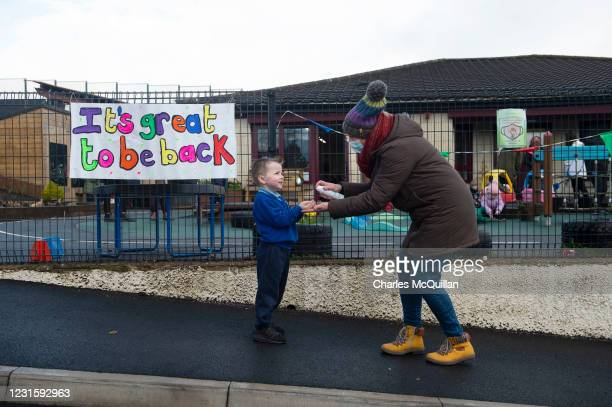 Head teacher Mrs Anderson sanitises childrens hands as they arrive at Hazelwood Integrated Nursery School on March 8, 2021 in Newtownabbey, Northern...