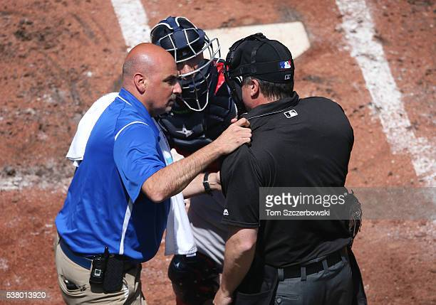 Head trainer George Poulis of the Toronto Blue Jays tends to home plate umpire Mike DiMuro after he was hit by a foul ball in the second inning as...