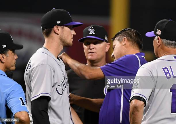 Head trainer Keith Dugger of the Colorado Rockies looks at pitcher Kyle Freeman after being hit by a line drive off the bat of JD Martinez of the...