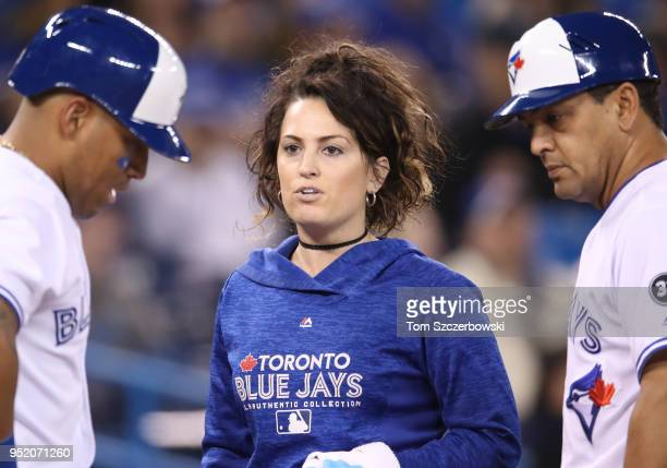 Head trainer Nikki Huffman of the Toronto Blue Jays checks on Yangervis Solarte after he was hit in the leg in the first inning during MLB game...