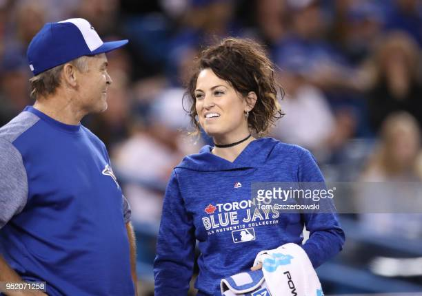 Head trainer Nikki Huffman of the Toronto Blue Jays talks to manager John Gibbons as she comes out onto the field in the first inning during MLB game...