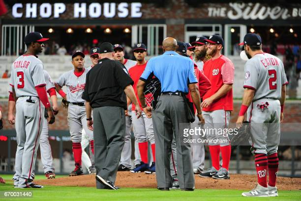 Head Umpire C B Bucknor tries to explain to members of the Washington Nationals the game has not ended due to a foul tip by Chase d'Arnaud of the...