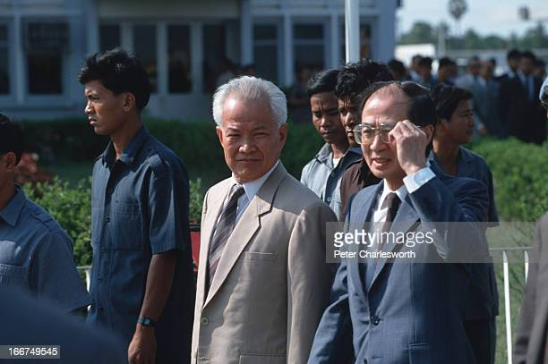 Head, Yasushi Akashi walks with Khieu Samphan as they head out to the Pochentong Airport runway to greet King Norodom Sihanouk on his arrival in...