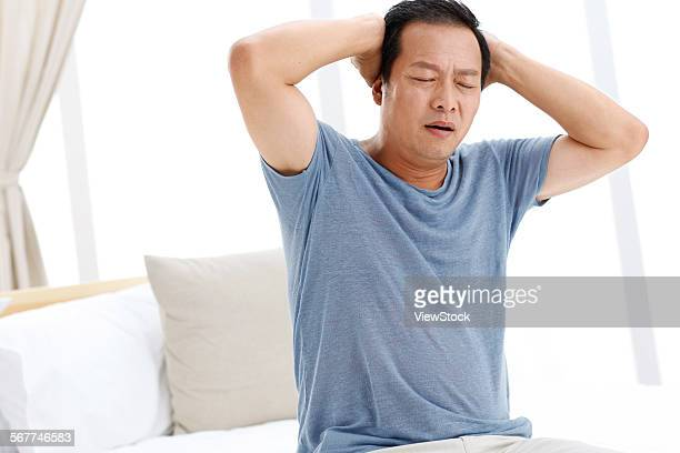A headache middle-aged man in the bedroom