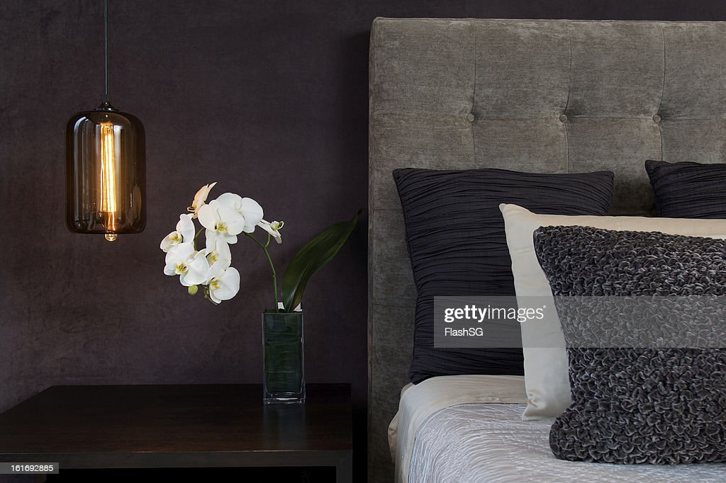 Headboard Detail with Pillows Lamp and Orchid Flowers : Stock Photo