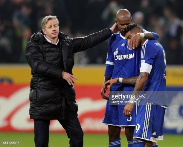 Headcoach Jens Keller of Schalke hugs Felipe Santana beside KevinPrince Boateng after the Bundesliga match between Borussia Moenchengladbach and FC...