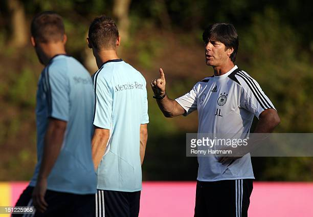 Headcoach Joachim Loew of Germany chats with Miroslav Klose and Lukas Podolski during a training session on September 04, 2012 in Barsinghausen,...