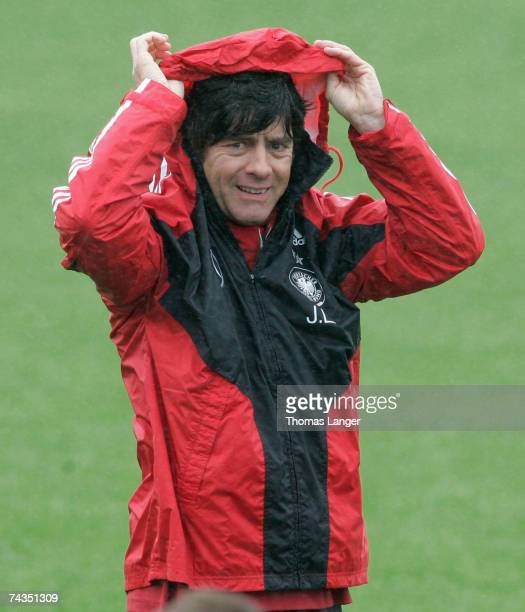 Headcoach Joachim Loew protects his hair from heavy rain during the German National Team training session at the AdidasStadium on May 29 2007 in...