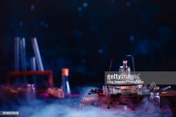 header with spirit lamp, magical scrolls, potion bottles, books and smoke in a dark magical still life. alchemy laboratory concept with copy space. - potion stock photos and pictures