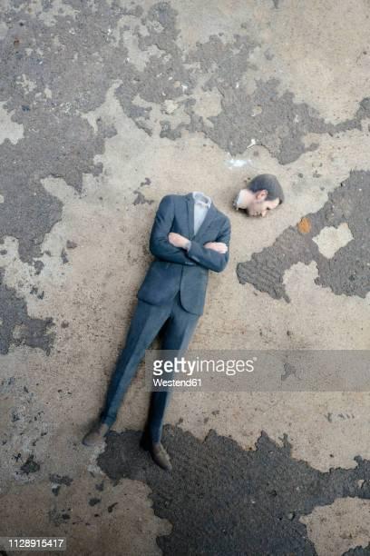 headless businessman figurine laying on cocrete - decapitado fotografías e imágenes de stock