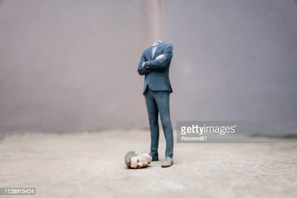 headless businessman figurine standing on cocrete - decapitado fotografías e imágenes de stock