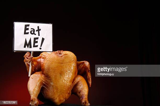 a headless cooked turkey holding a sign that says eat me  - funny turkey images stock photos and pictures