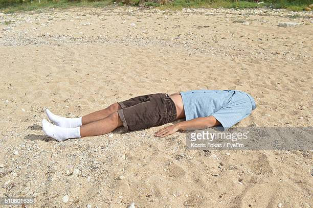 Headless man lying on sandy beach