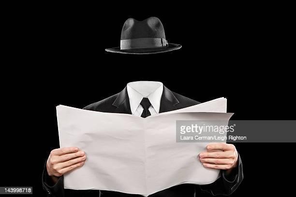 A headless man reads a blank newspaper