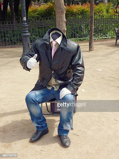 Headless man sitting in park showing thumbs up