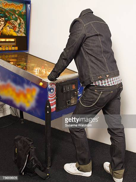A headless person dressed in denim playing flipper.