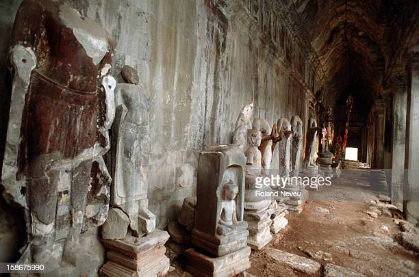Headless sculptures looted by ancient art thieves among the ruins at the 'Gallery of Thousand Buddhas' in the courtyard of Angkor Wat