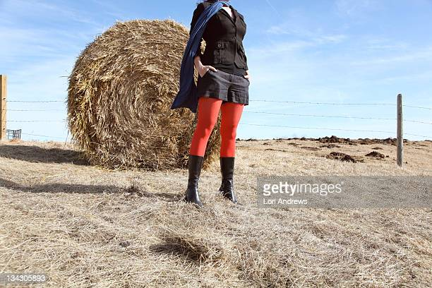 Headless woman in red tights with hay bale