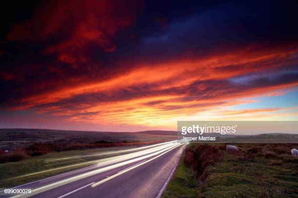headlight trails on moorland road at sunset, reynoldston, gower, wales - gower peninsula stock photos and pictures