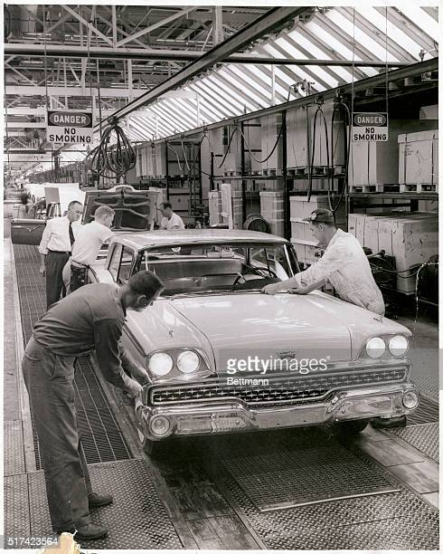 Headlights are adjusted and the car is given final inspection just before it rolls from a Ford Motor Company final assembly line into the haulaway...