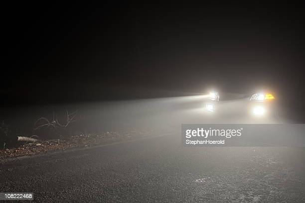 Headlights of a car driving in the fog at night