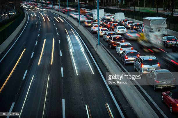 Headlights shine as traffic moves during rushhour early in the morning on January 8 2015 in Barcelona Spain The Spanish labor market has finally...