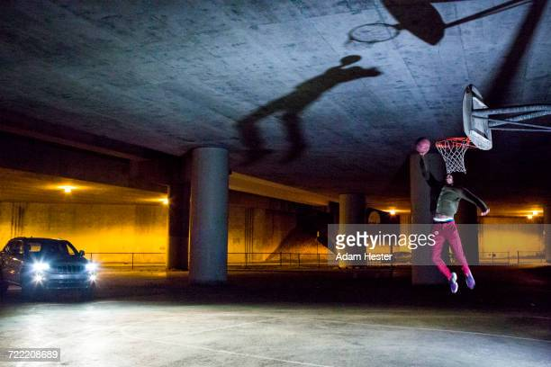 headlights shining on black man dunking basketball - trefferversuch stock-fotos und bilder