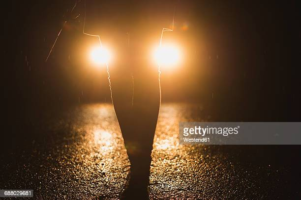 Headlights shining on legs of a woman at night