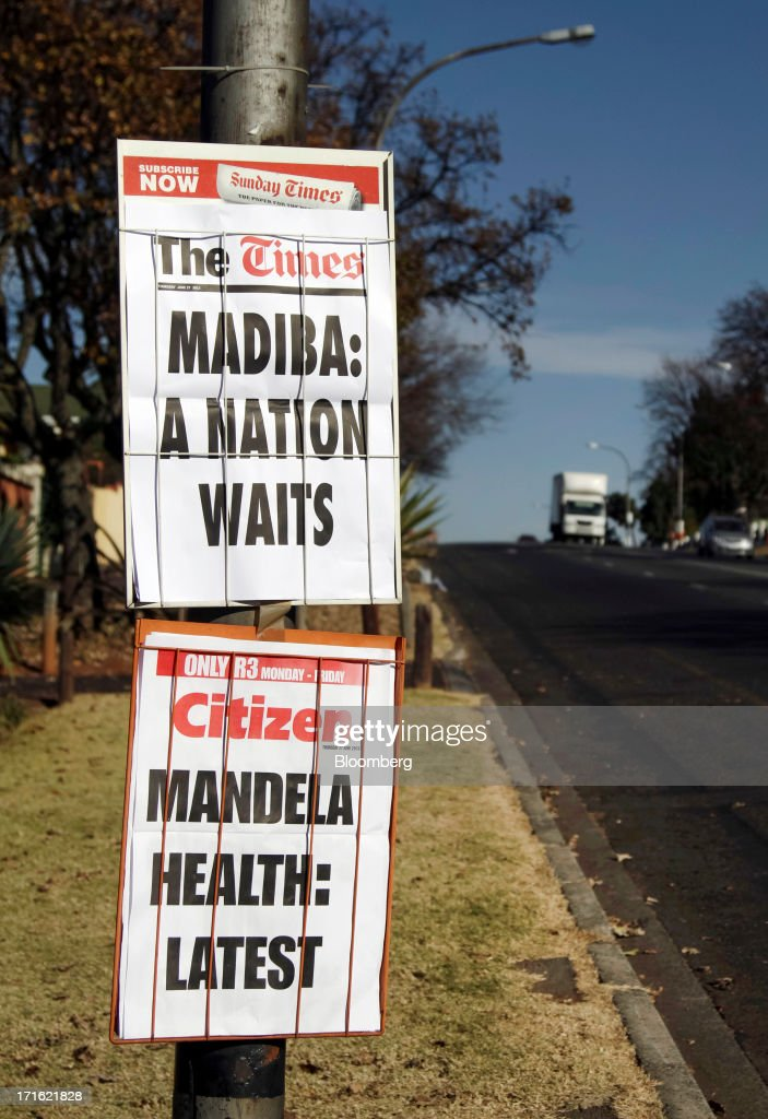 Headlines reporting on the health of former president Nelson Mandela are displayed on South African newspaper's posters secured to a telegraph pole in Johannesburg, South Africa, on Thursday, June 27, 2013. South African President Jacob Zuma cancelled a trip to neighbouring Mozambique today after visiting Nelson Mandela, who remains critically ill in the hospital. Photographer: Nadine Hutton/Bloomberg via Getty Images