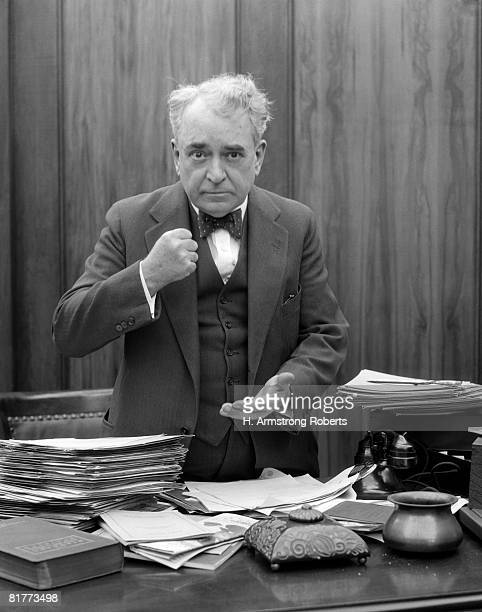 Head-On Picture Of Angry Businessman, Sitting Behind A Desk And Making A Fist.