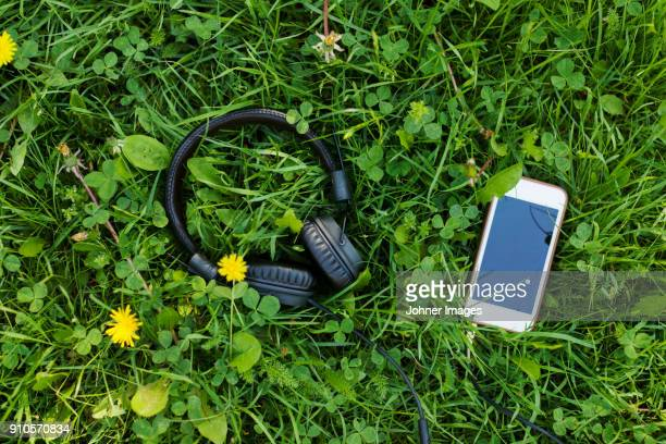 Headphones and mobile phone lying in grass