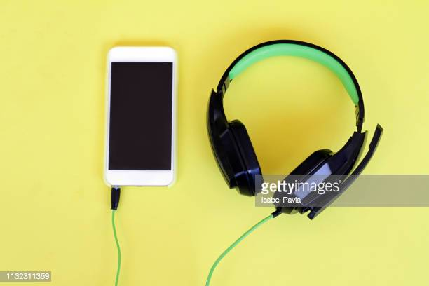 headphones and smart phone over yellow background - musical equipment stock pictures, royalty-free photos & images