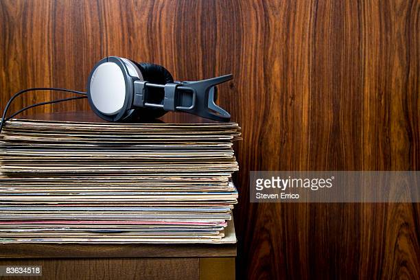 Headphones laying on stack of vinyl records