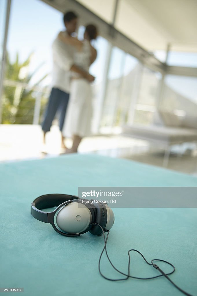 Headphones on a Turquoise Sofa, Couple Dancing in the Background : Stock Photo