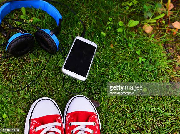 Headphones, smart phone and sport shoes on grass