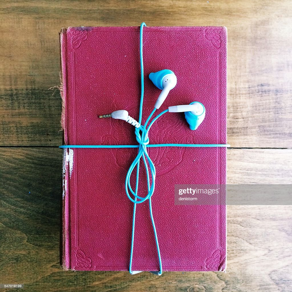Headphones wrapped around an old book : Stock Photo