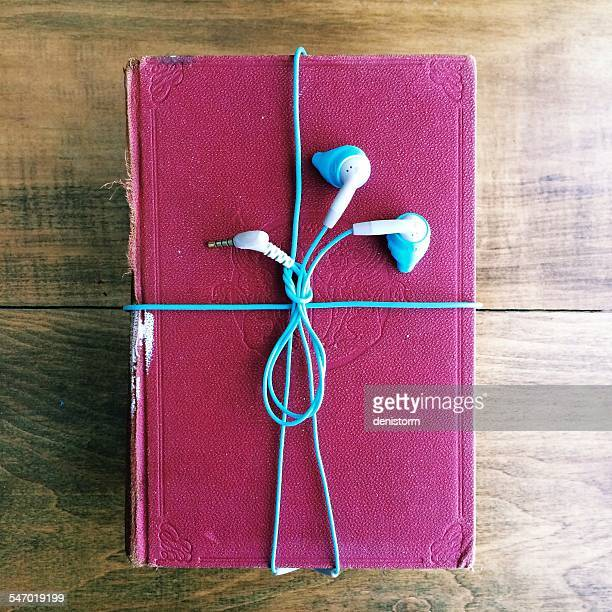 Headphones wrapped around an old book