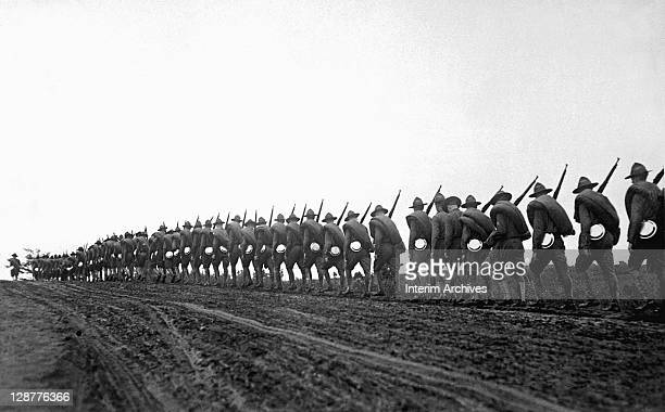 Headquarters Troop of the 27th Division, New York National Guard, are silhouetted in a line as they march to the training camp, September 1917.