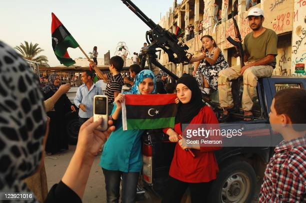Headscarved girls pose for a photograph with a rebel soldier as Libyan revolution tourists continue to celebrate the fall of Colonel Muammar Gaddafi...