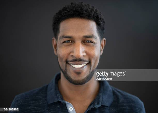 headshot of 44 year old mixed race man in casual polo shirt - looking at camera stock pictures, royalty-free photos & images