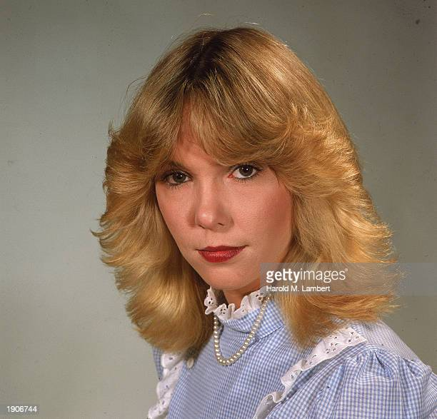 Headshot of a blonde woman with a feathered hairstyle wearing a lace trimmed blouse late 1970s